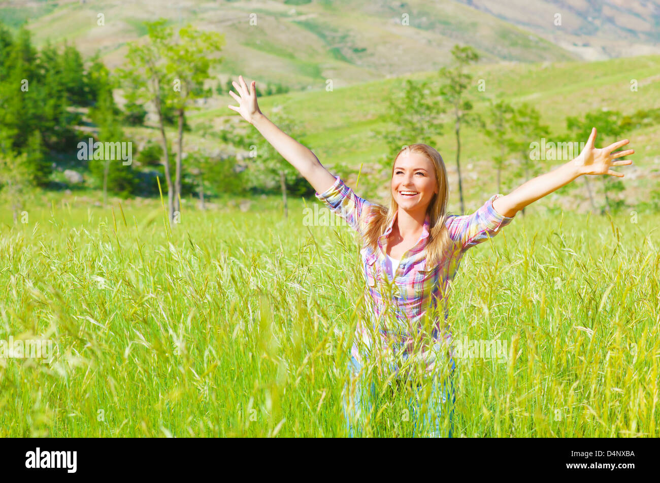 Female enjoying green field, hands up in fresh air, standing in spring wheat grass, freedom and happiness concept - Stock Image