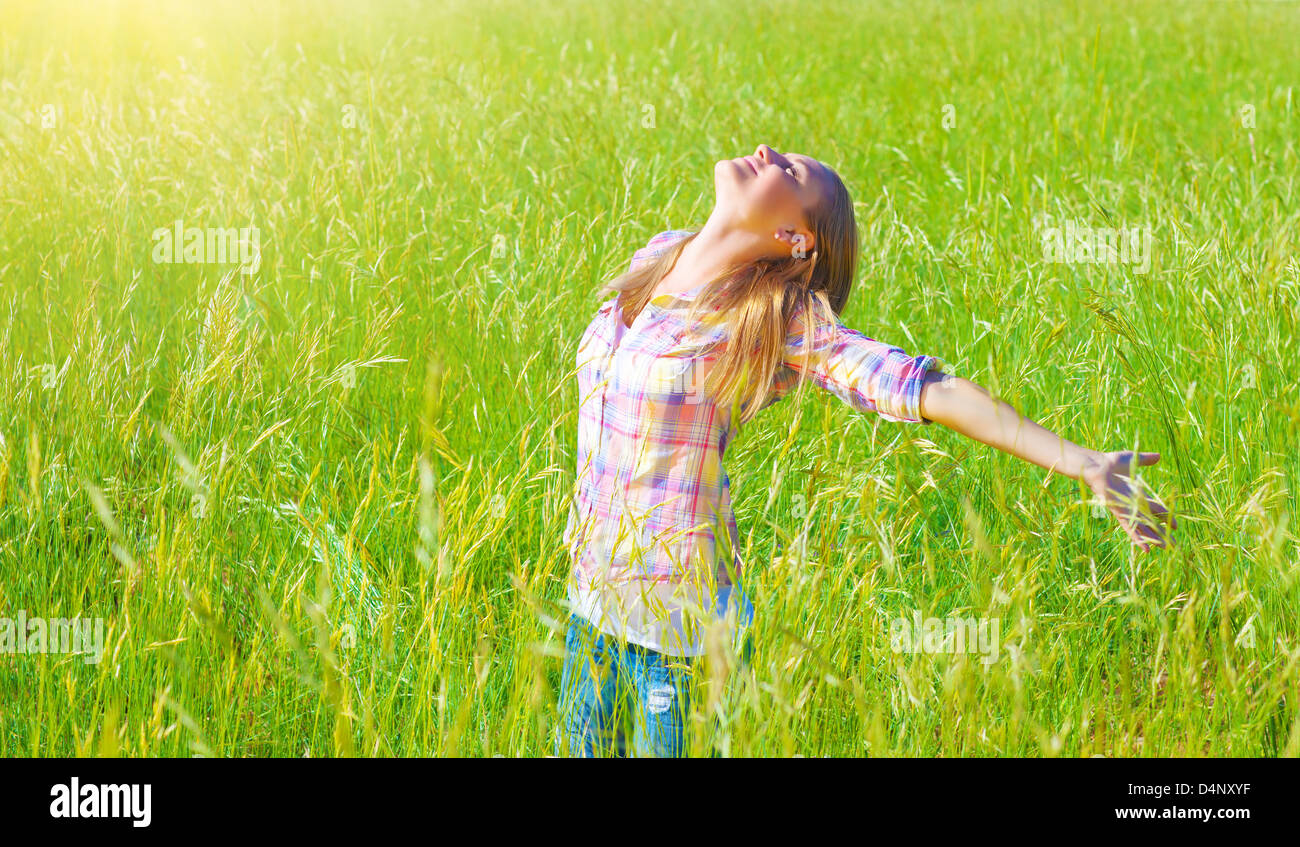 Woman having fun outdoor, enjoying fresh air and spring green grass, freedom and happiness concept - Stock Image