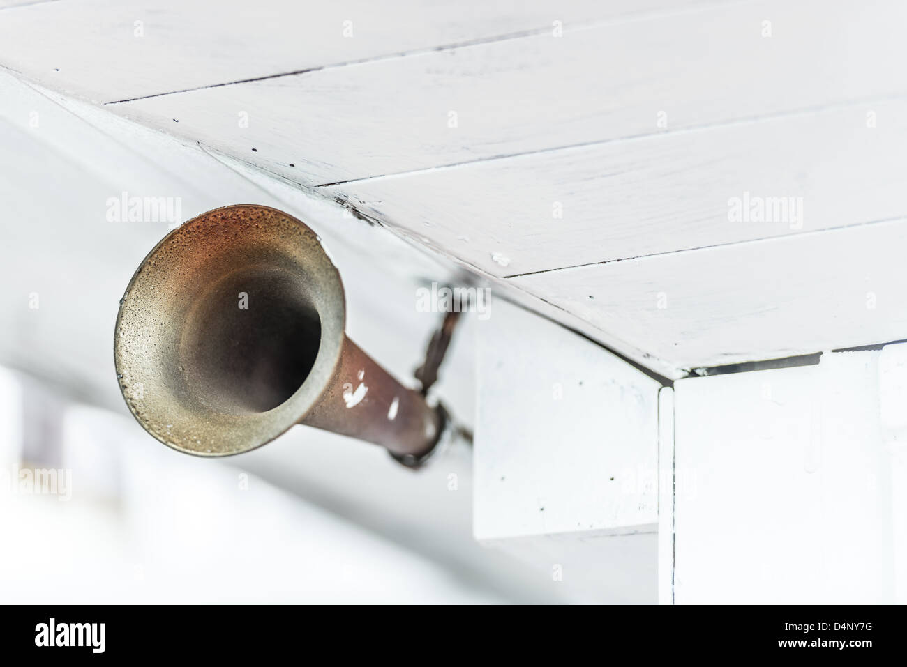 Close up view of old grungy metal horn on ship under old white wooden ceiling. Sound signal during sea travelling. - Stock Image