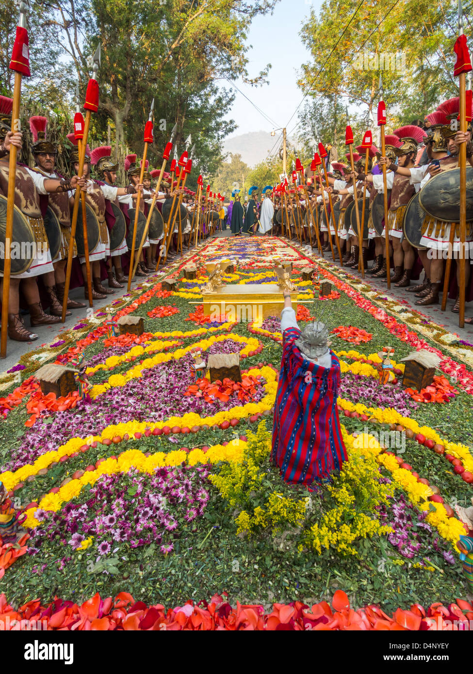 Roman guards line a traditional street carpet or 'alfombra' during Semana Santa easter celebrations in Antigua, - Stock Image