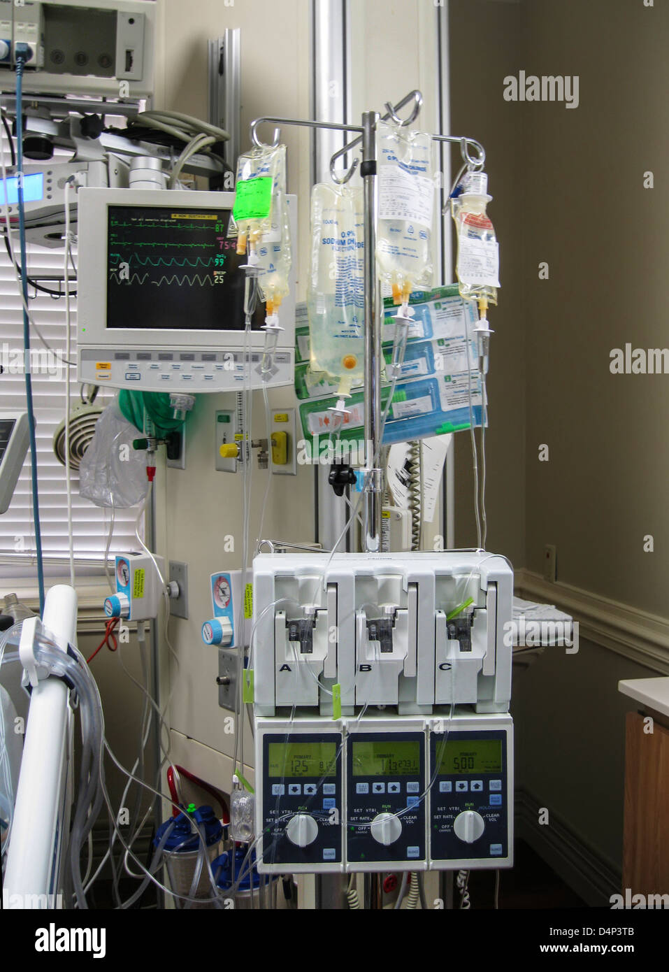 Multiple IV drips and cardiac monitor inside the ICU - Stock Image