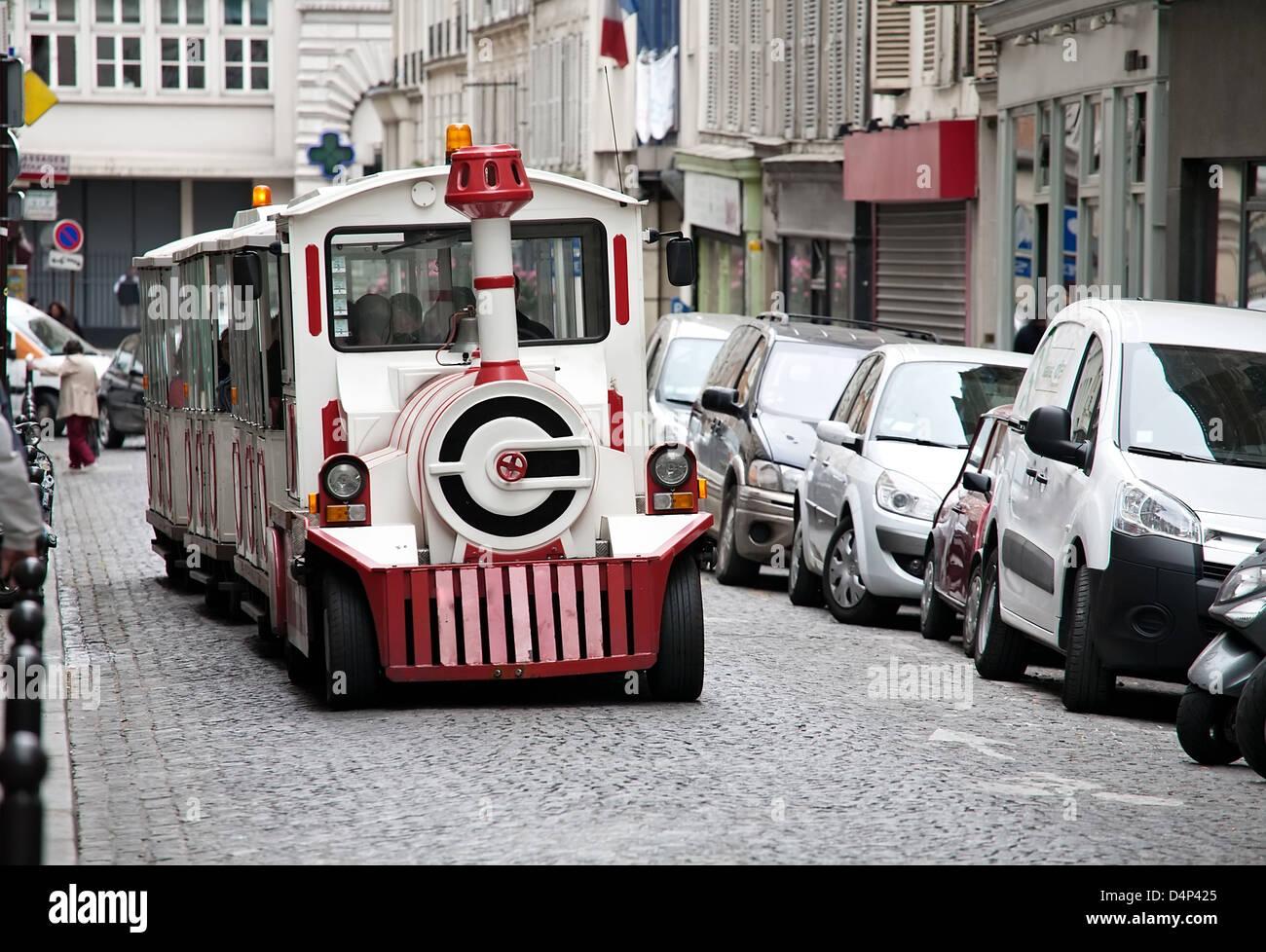 small city tour tourist train on street of old Paris - Stock Image