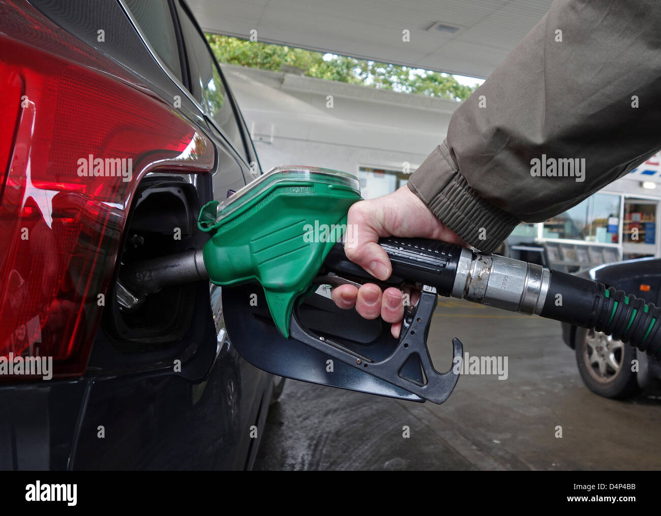 Man using petrol pump at petrol station, uk - Stock Image