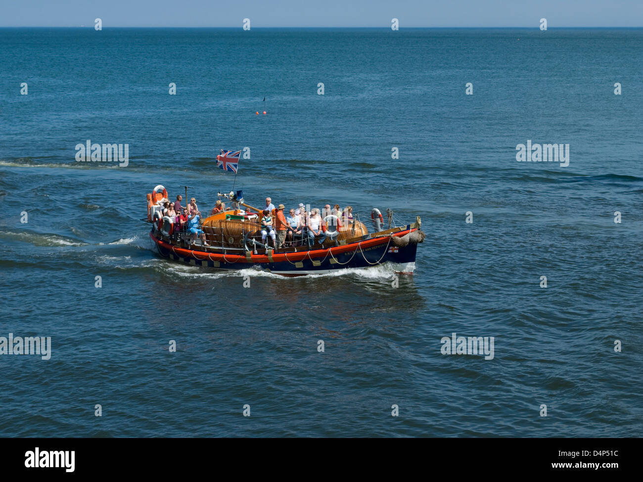 tourists aboard former lifeboat  'Mary Ann Hepworth' on a pleasure trip around Whitby Harbour and Bay - Stock Image