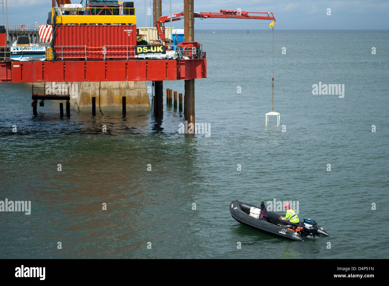 Marine safety boat and piling rig on Whitby Harbour Stock Photo