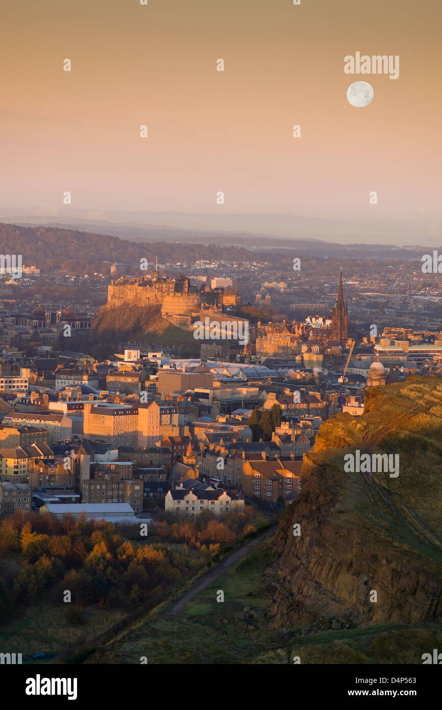 castle and moonrise from salisbury crags at dusk - Stock Image