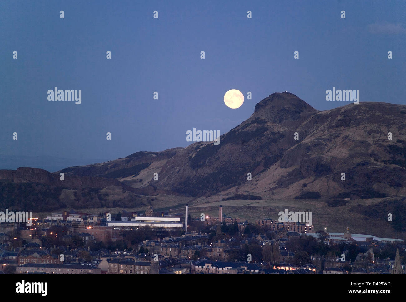dusk view from blackford hill across city by newington to arthur's seat with moonrise and commonwealth pool - Stock Image