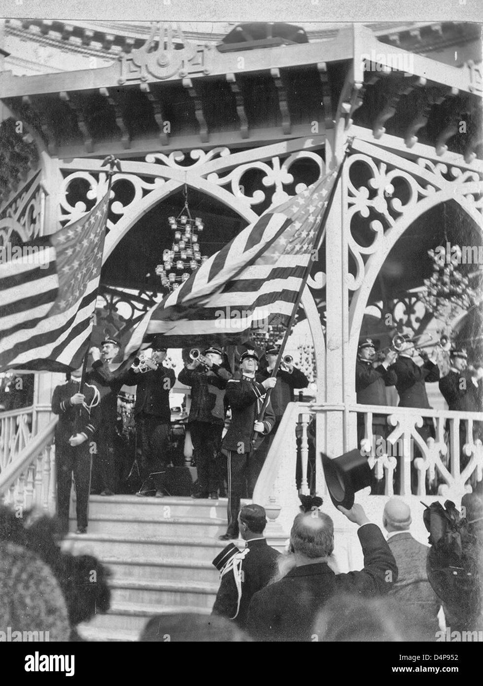 John Philip Sousa Band playing on bandstand while two band members stand on stairs, waving American flags - Paris - Stock Image