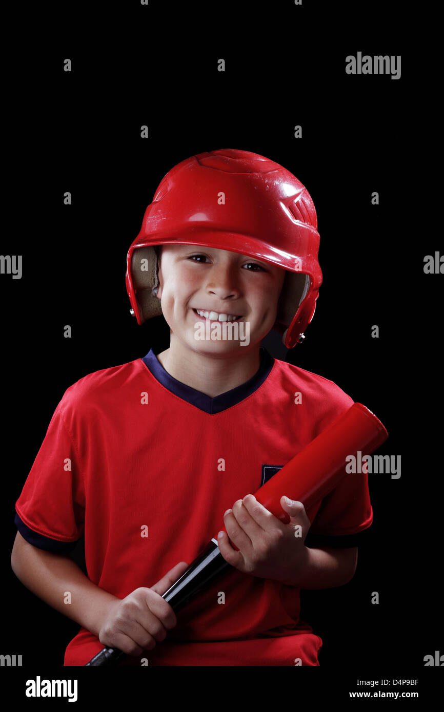 Smiling young boy with red baseball bat on black background - Stock Image