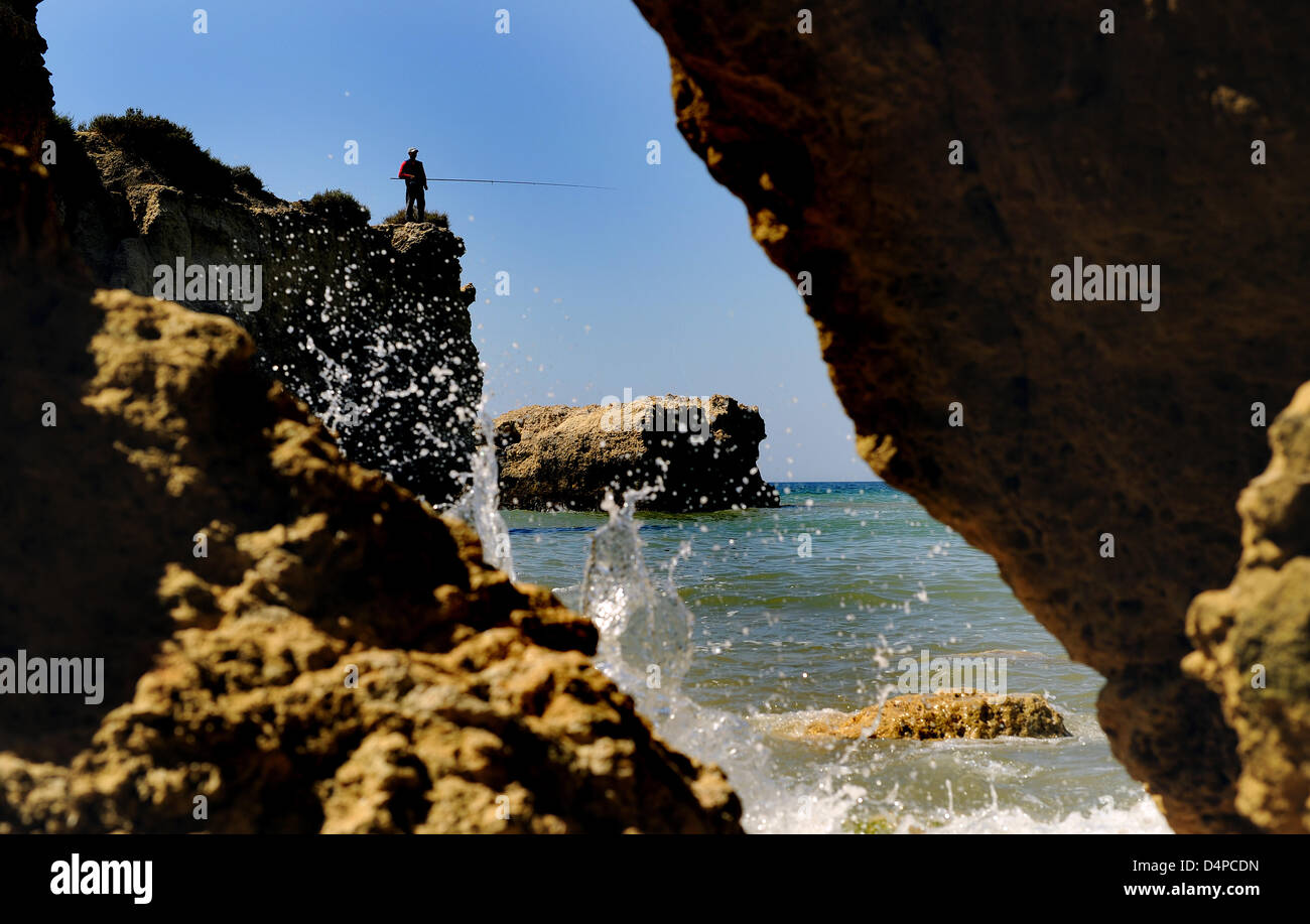 A fisher with an angling rod stands on a rock in a cove of a beach near Albufeira, Portugal, 05 May 2009. Photo: - Stock Image