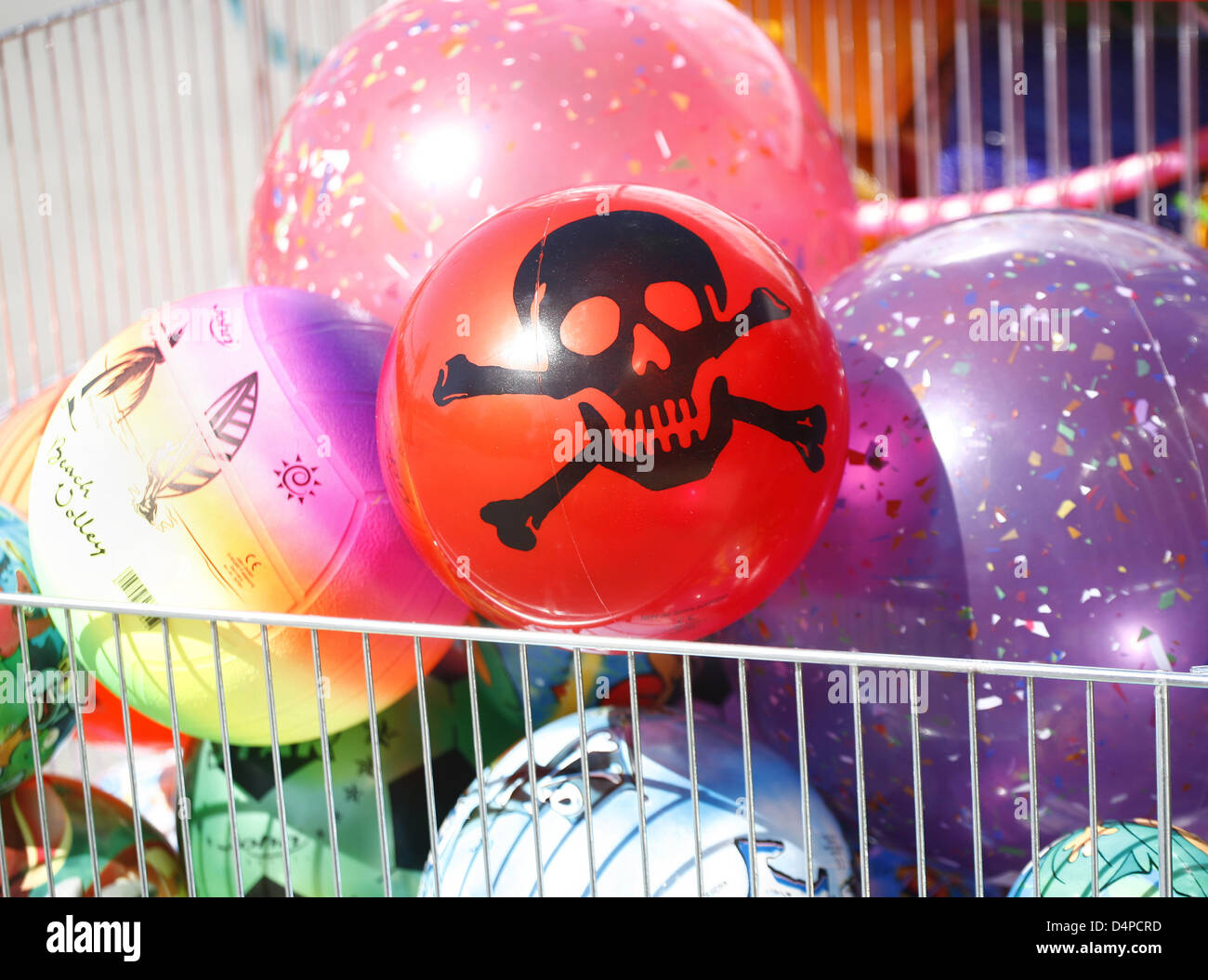 A cheap red plastic ball with a death skull printed on pictured in St. Peter Ording, Germany, 13 May 2009. Time - Stock Image