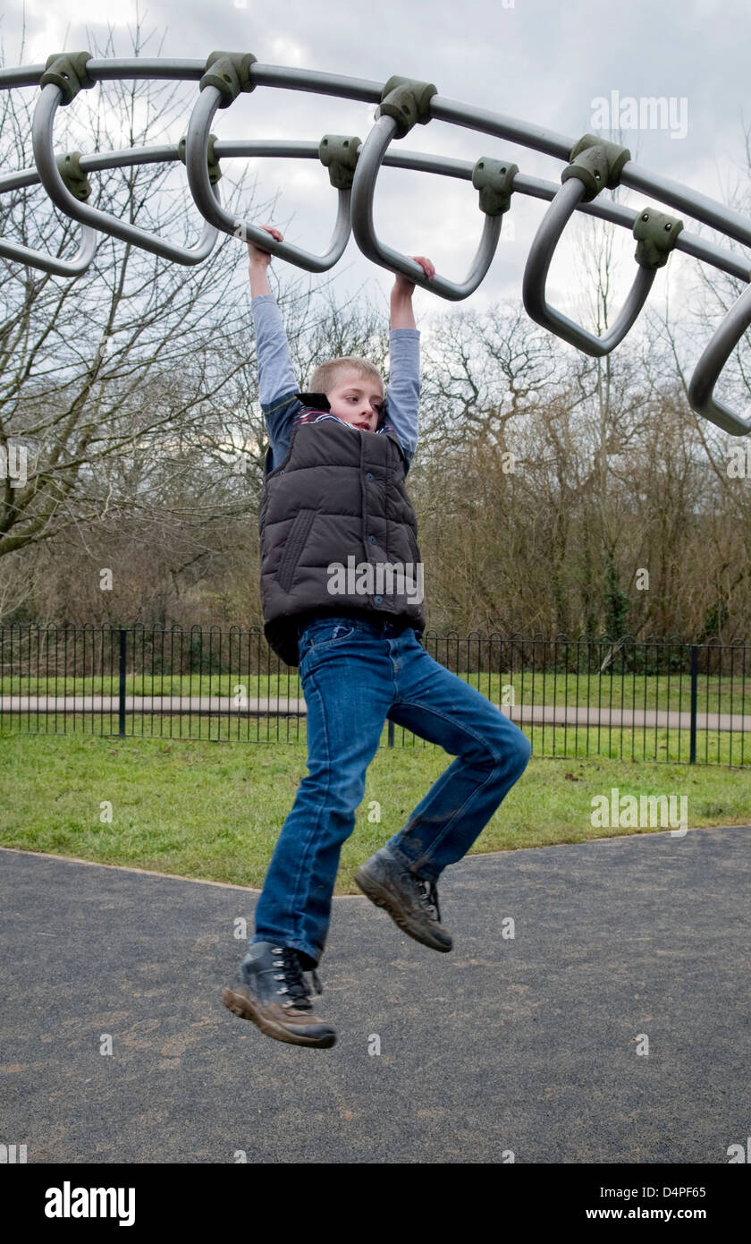 Young 10 year old Caucasian boy swinging across climbing frame in park in Bristol, UK - Stock Image