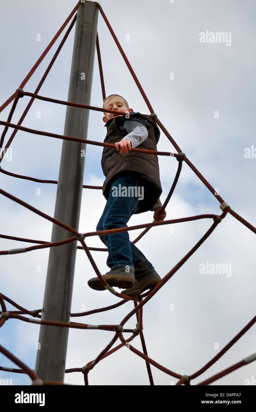 Young 10 year old Caucasian boy climbing on a rope climbing frame in ...