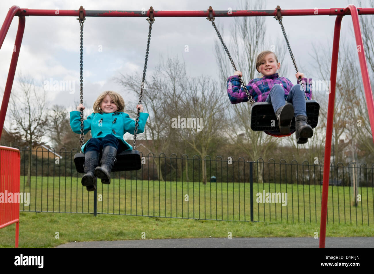 Two 8 year old Caucasian girls having fun playing on swings in park in Bristol, UK - Stock Image