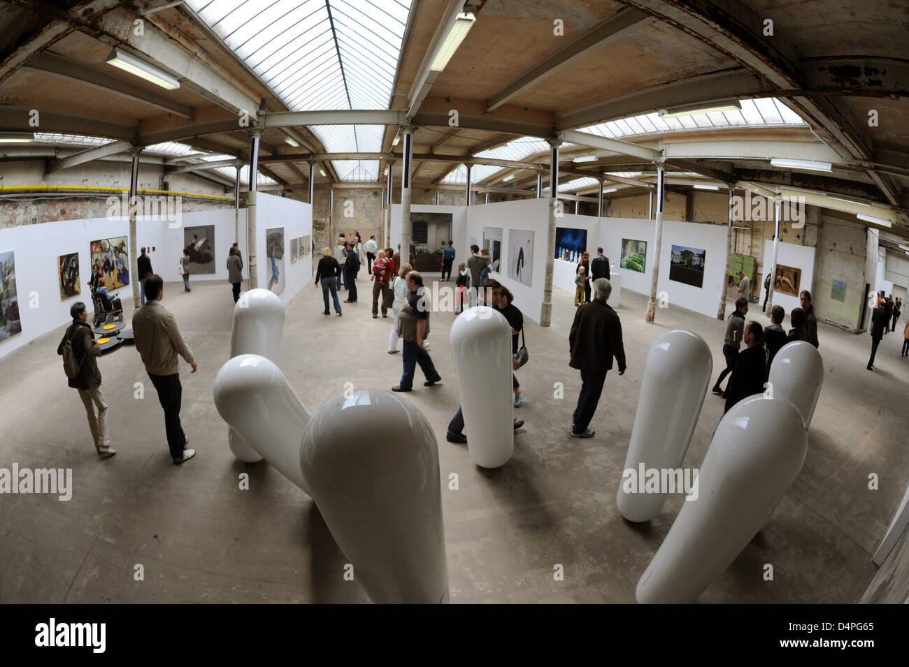 Visitors take a look at an art exhibition at the former cotton spinning works ?Baumwollspinnerei?, an industrial - Stock Image