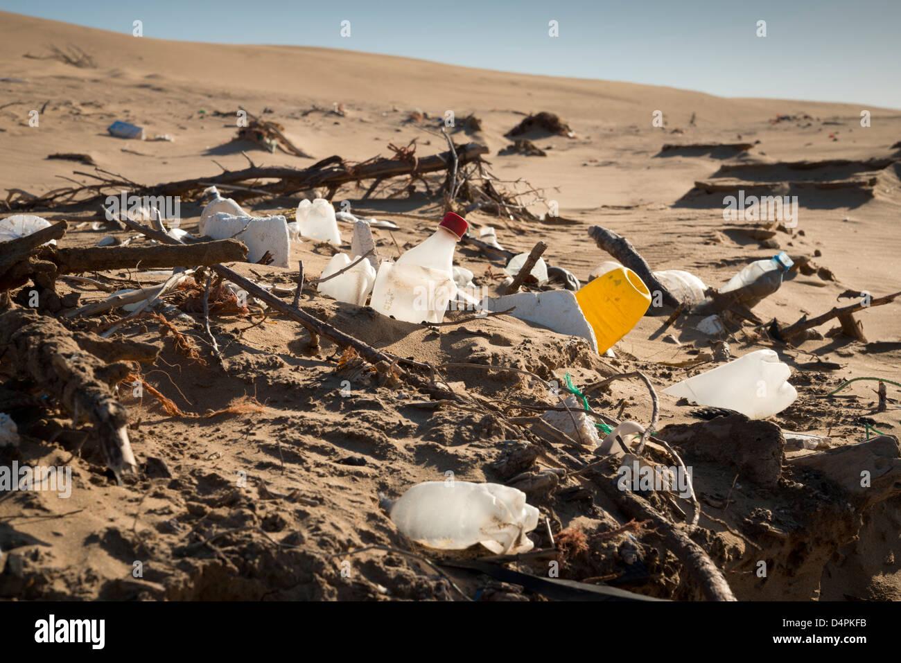 Flotsam and jetsam on a beach. Washed up plastic bottles. - Stock Image