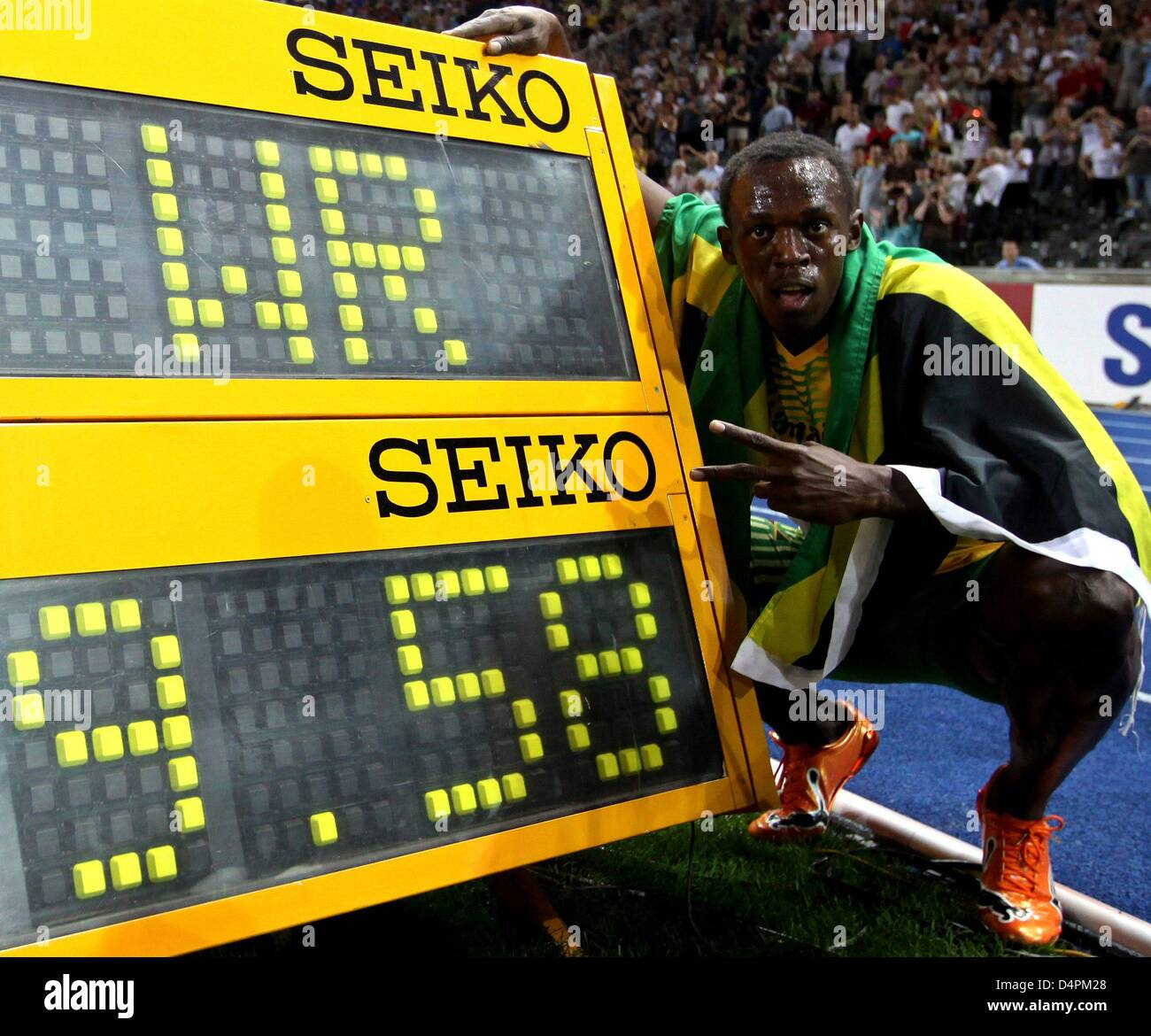 Jamaican Usain Bolt poses next to the display of his new ...