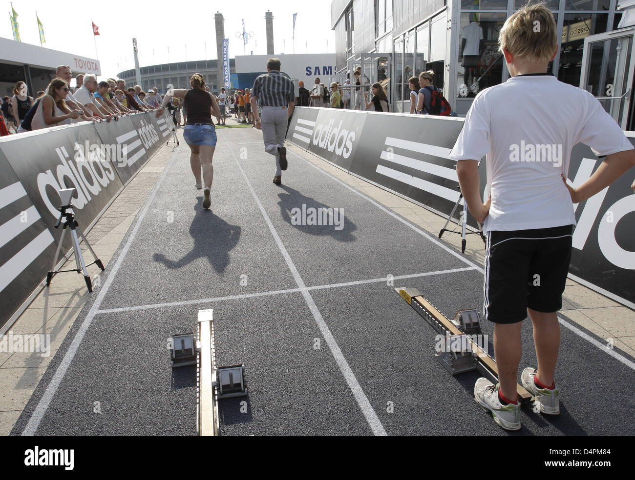 Visitors test a track during the 12th IAAF World Championships in Athletics outside the Olympic Stadium in Berlin, - Stock Image