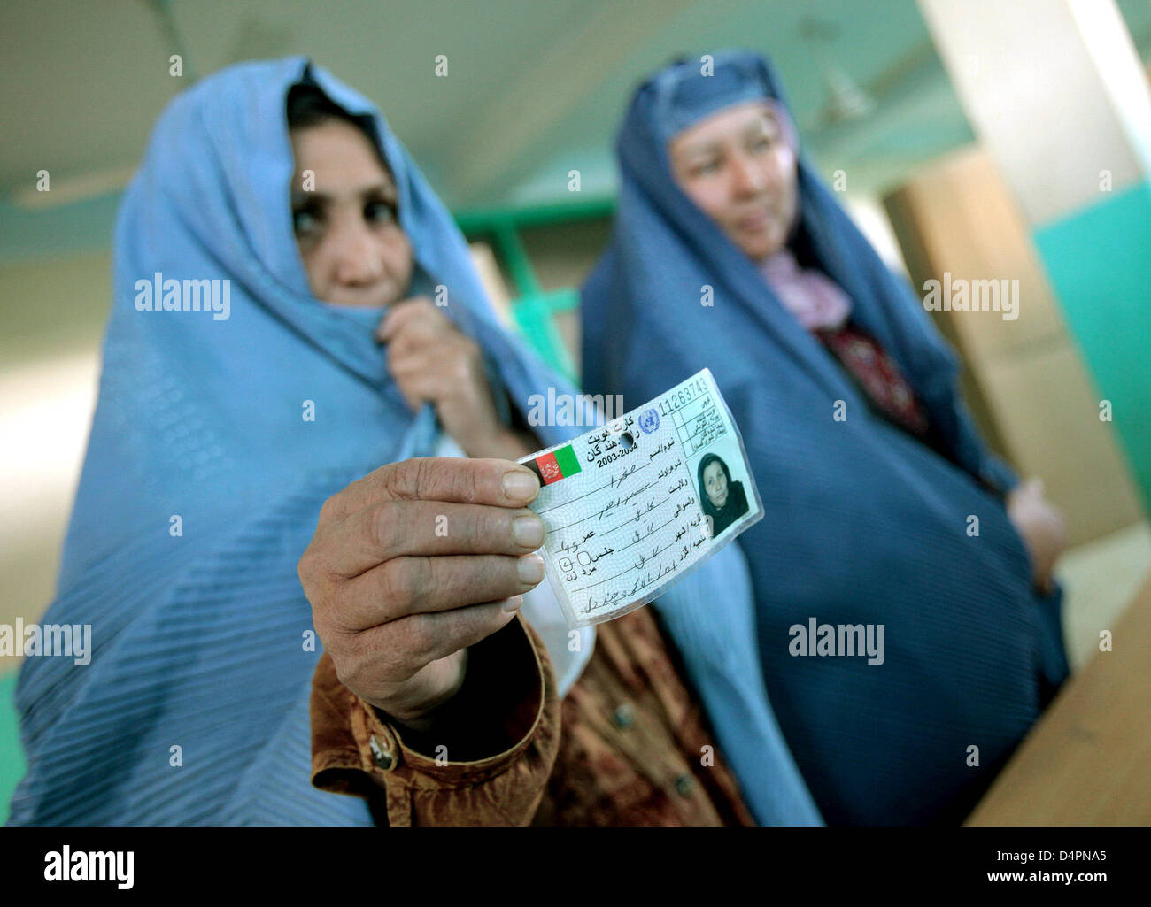 Afghan women hold their identity cards while they wait at a polling station in a mosque in Kabul, Afghanistan, 20 - Stock Image