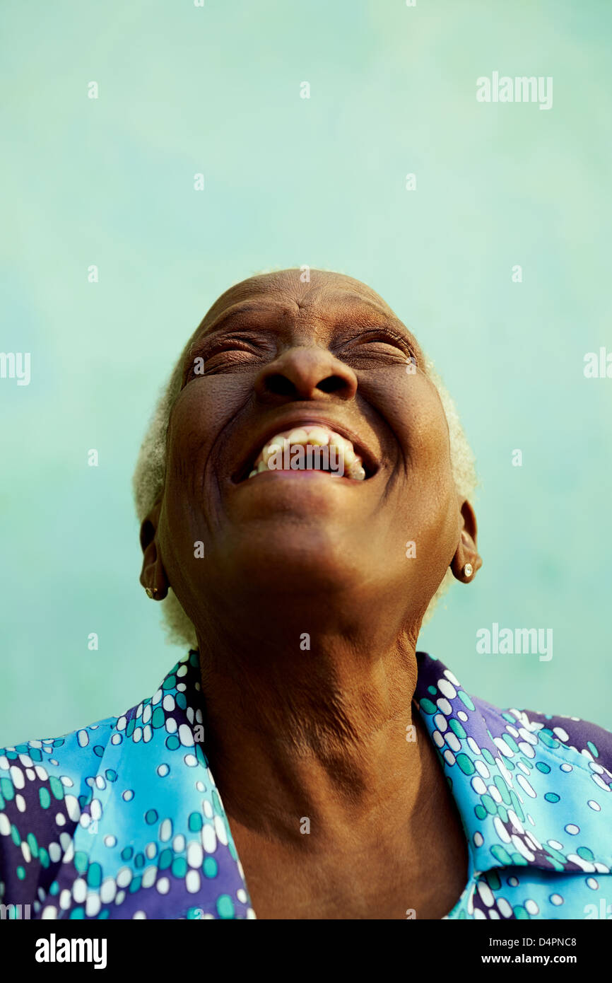 Old people and emotions, portrait of bizarre senior african american lady laughing with head tilted up. Copy space - Stock Image