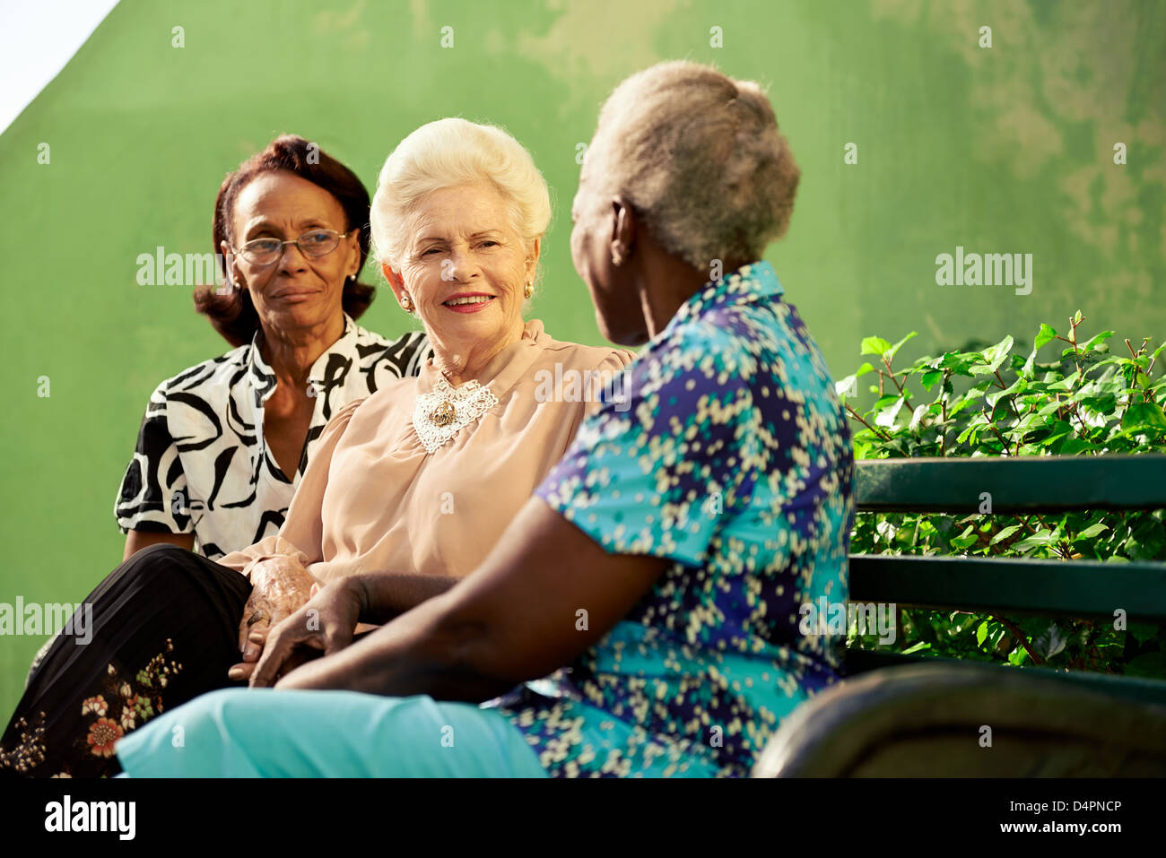 three old women sitting on bench in park and talking - Stock Image