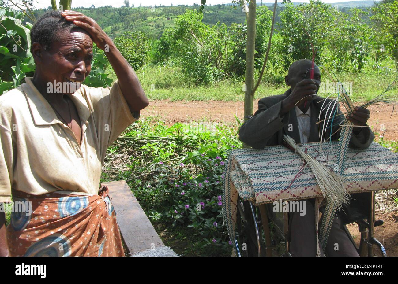 Pierre Celestine Karimumrumba and his wife Stephania Mukantenera bind straw mats in front of their house in Gahanga, - Stock Image