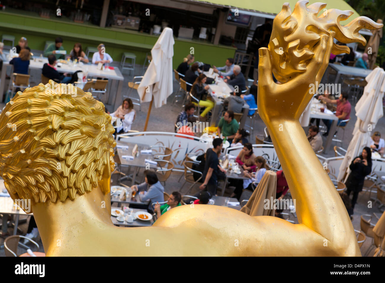 Prometheus statue from behind with diners at the Rockefeller Center. - Stock Image