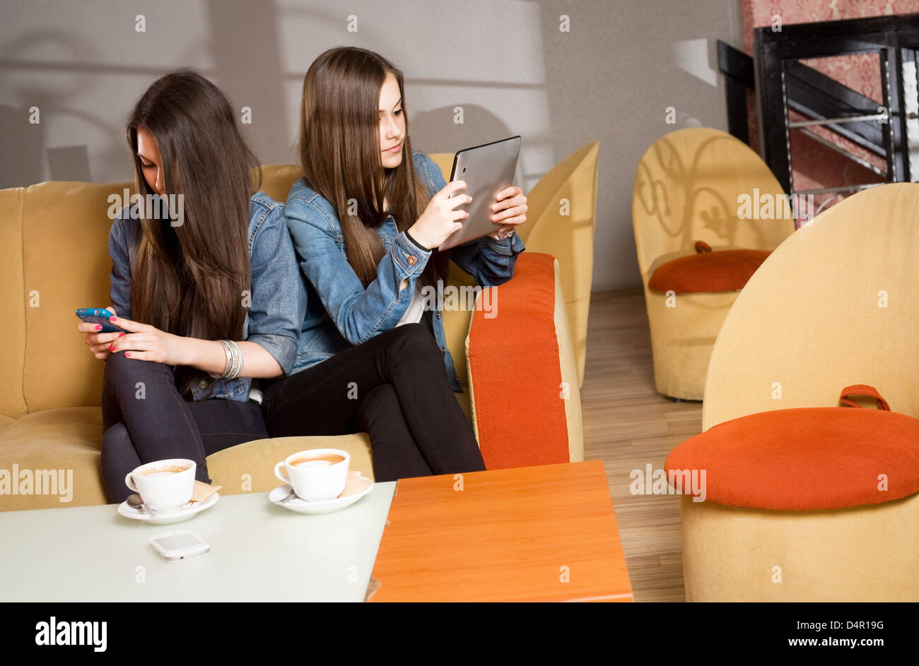 Two girls getting lost in and separated by their mobile devices. Stock Photo