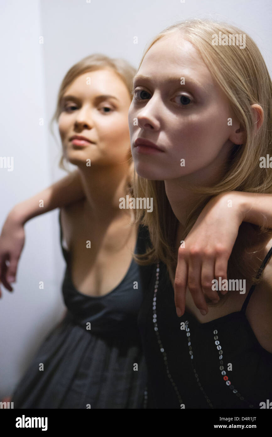 Young woman with arm around friend's shoulder, portrait - Stock Image