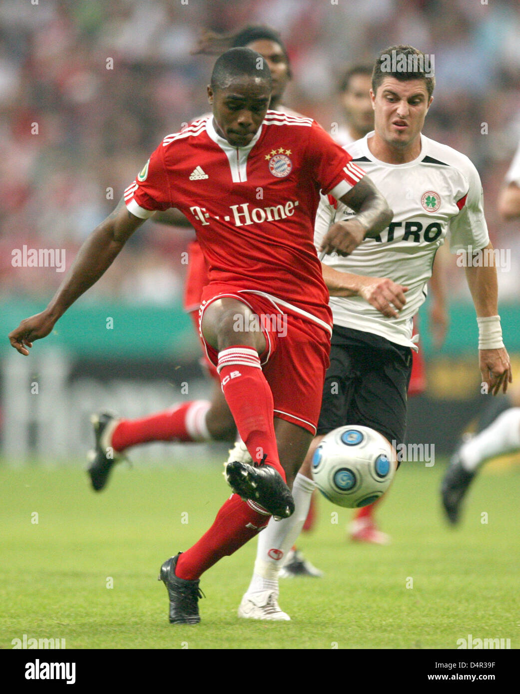 Munich?s Edson Braafheid (L) fights for the ball with Oberhausen?s Moritz Stoppelkamp during the German DFB Cup - Stock Image