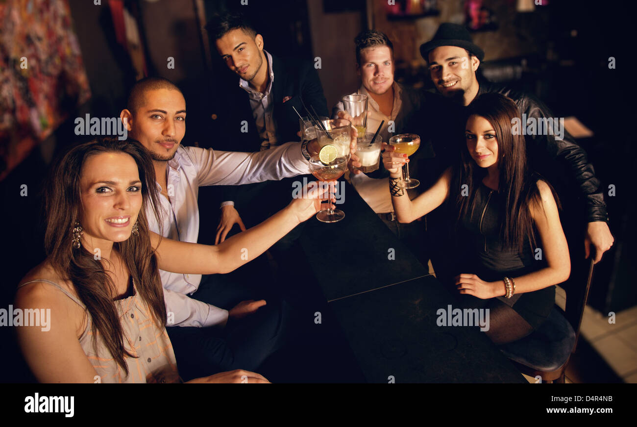 Group of friends at the bar raising their glass for a toast - Stock Image