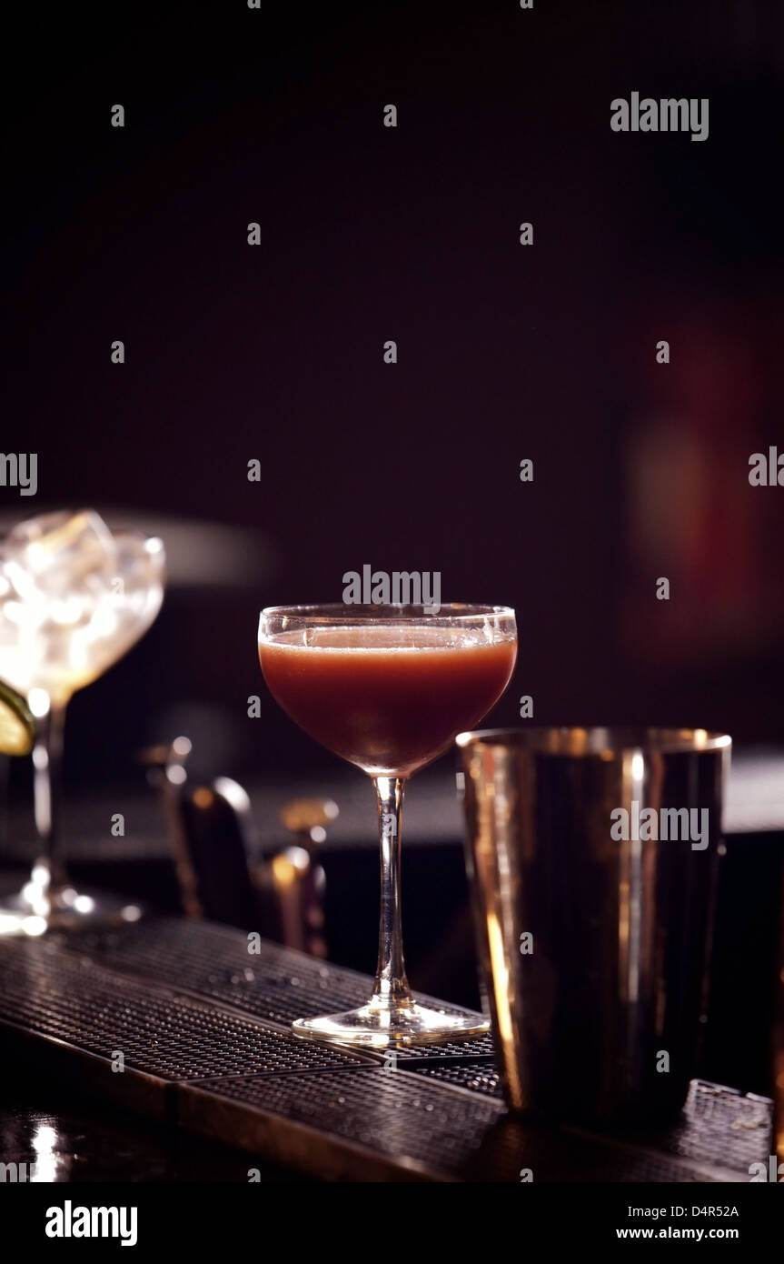 Glass of red wine with shaker on dark background - Stock Image