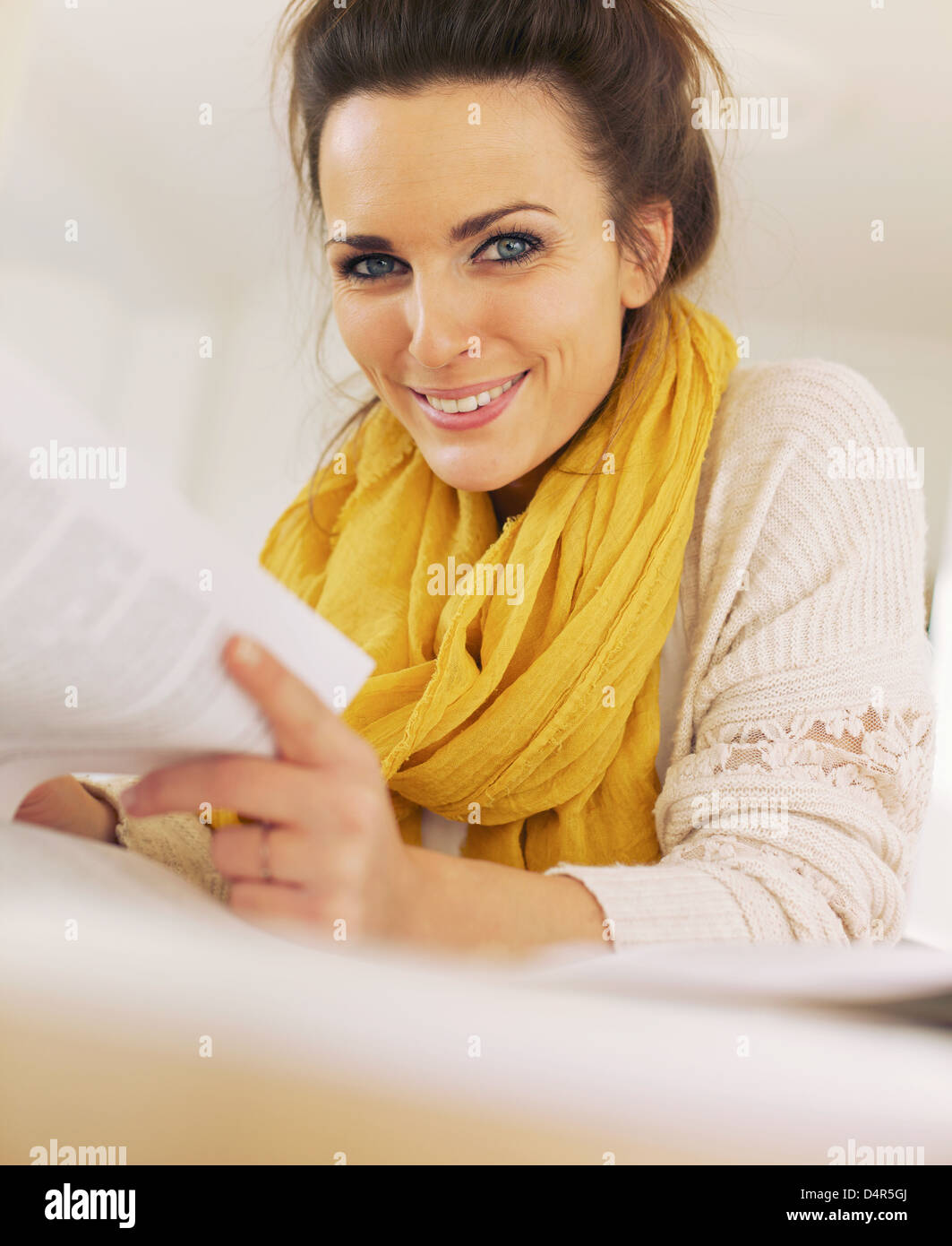 Reader turning the book's pages while looking at the camera - Stock Image