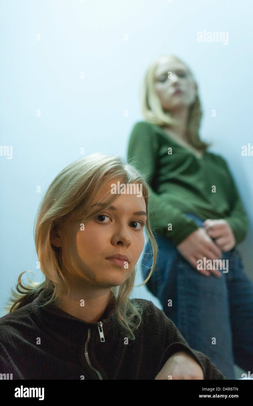 Teenage girl looking at camera, friend in background - Stock Image