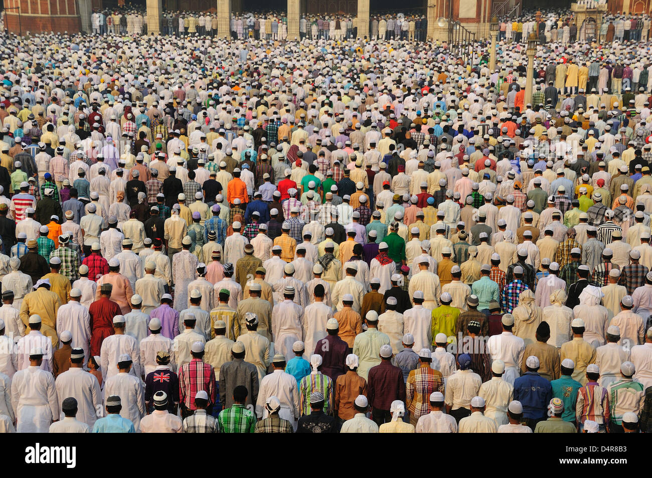 Thousands of Muslim people praying inside and outside of the Mosque to celebrate end of Ramadan. - Stock Image