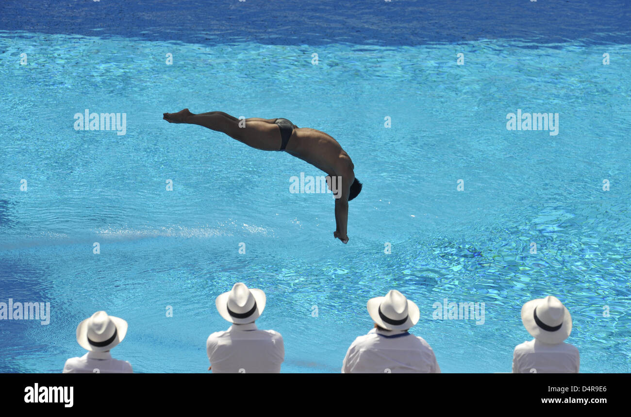 Judges watch as Chinese He Chong performs during the 3m