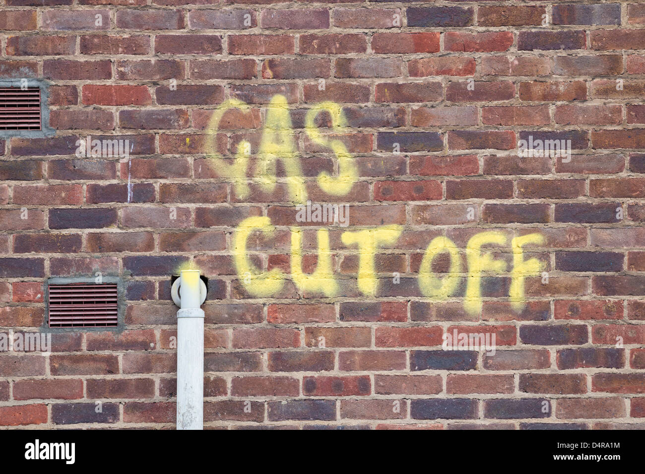 Gas cut off painted on building wall near pipe - Stock Image