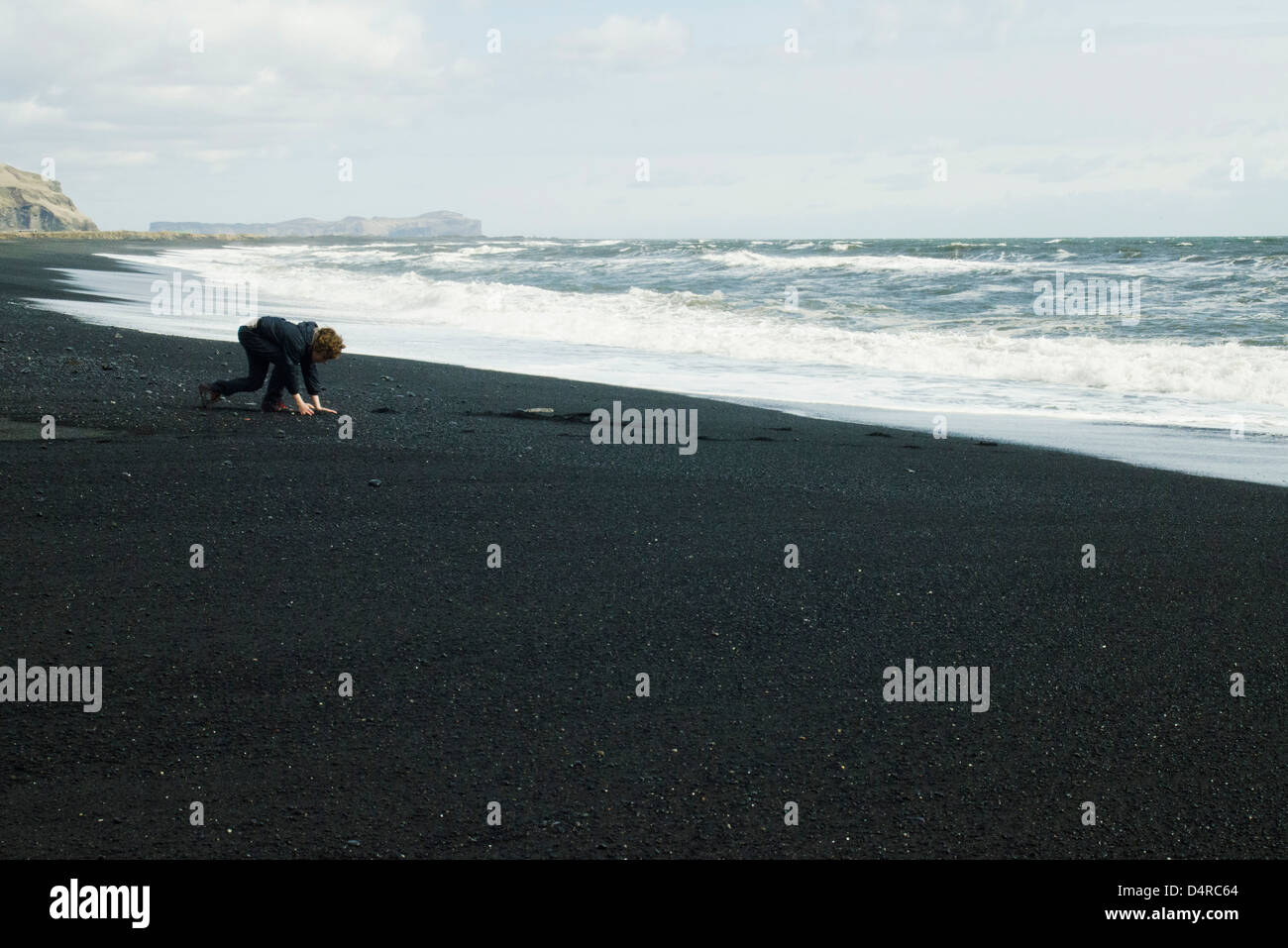 Boy picking up the black sand beach, Iceland - Stock Image