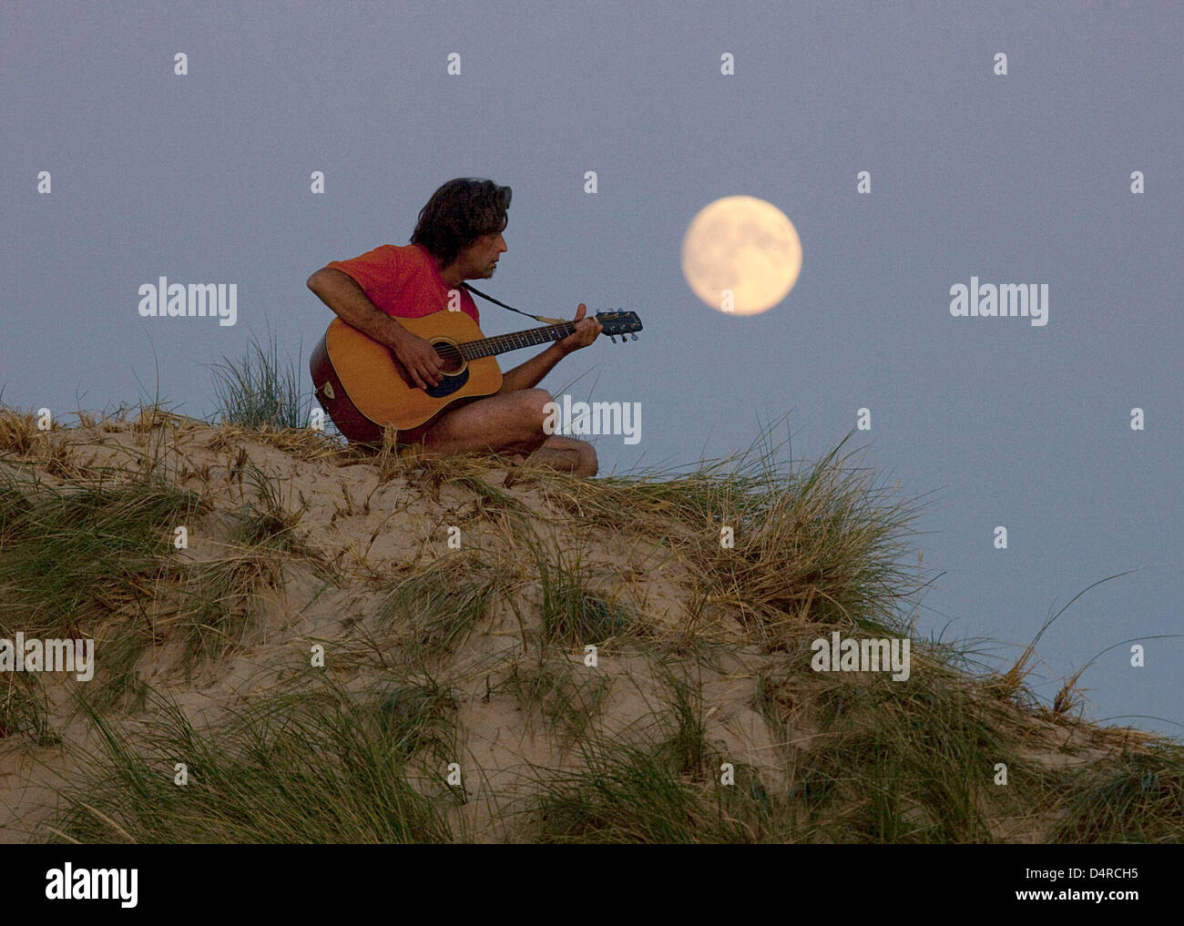 A Bohemian troubadour sits on a sand dune and serenades under the full moon on Amrum island, Germany, 04 August - Stock Image