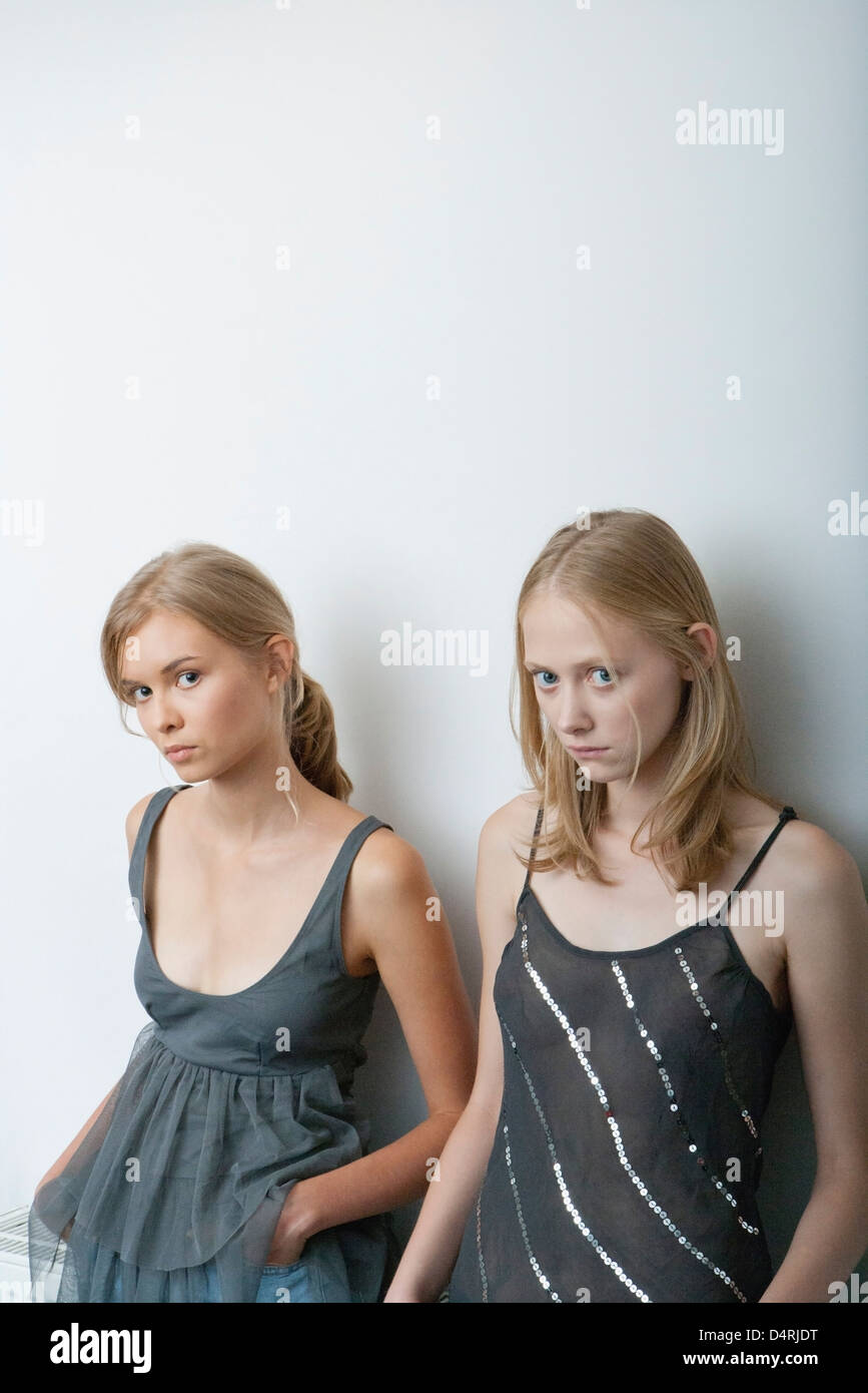 Young woman and teenage girl leaning against wall, looking warily at camera - Stock Image