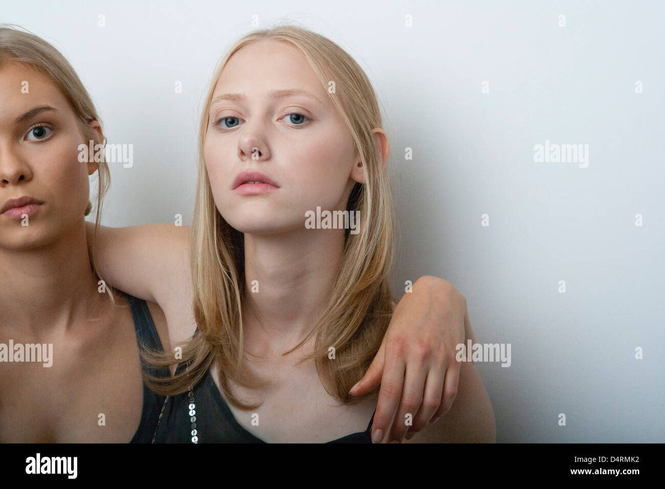 Young woman with arm around girlfriend's shoulder, portrait - Stock Image