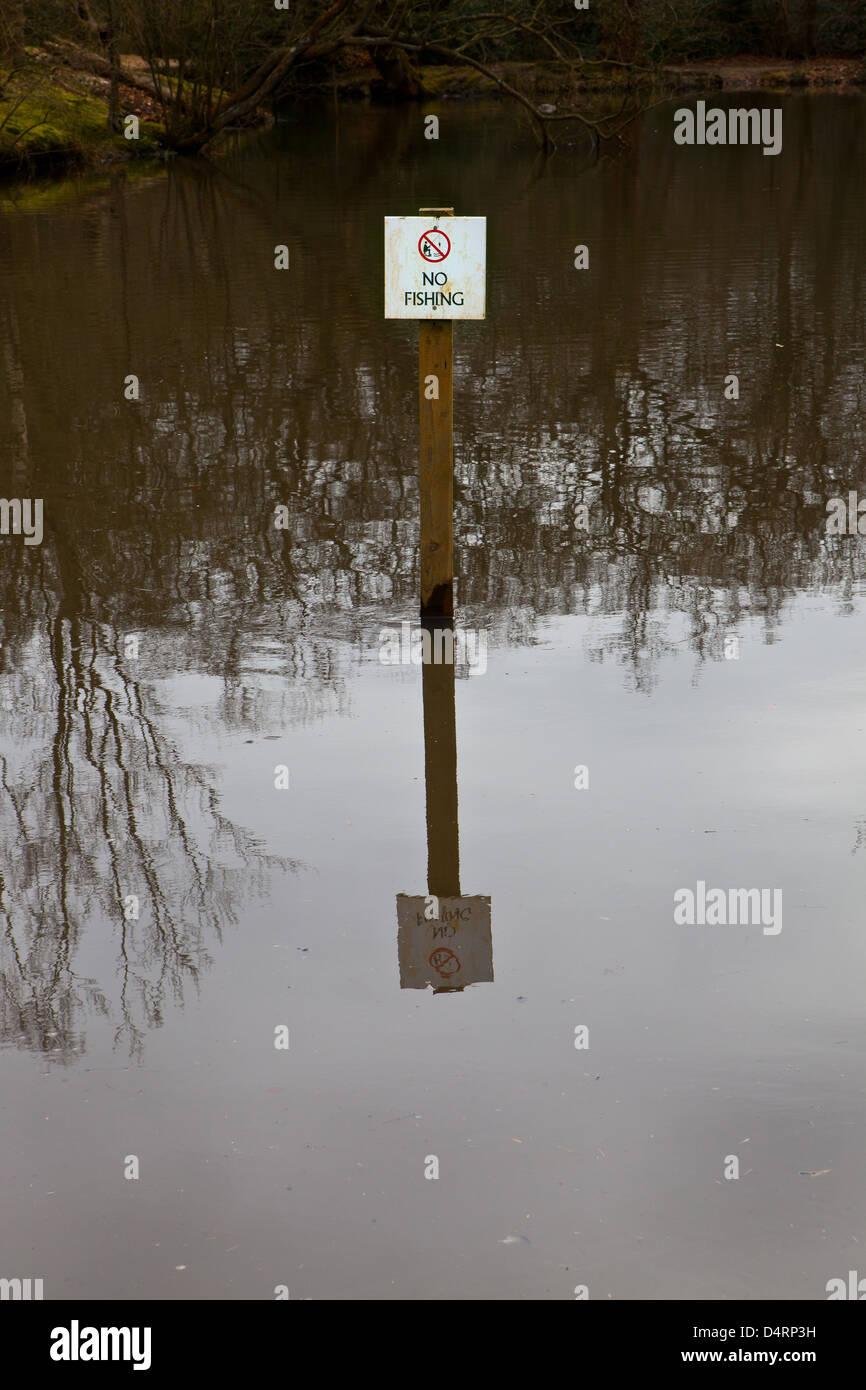 No fishing sign in the middle of a dark and deep pond with its reflection - Stock Image