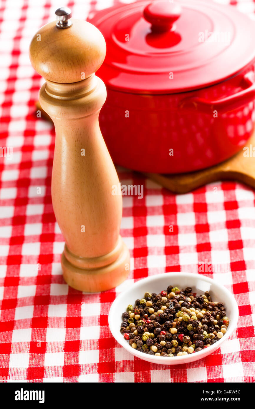 pepper and wooden pepper mill on kitchen table - Stock Image