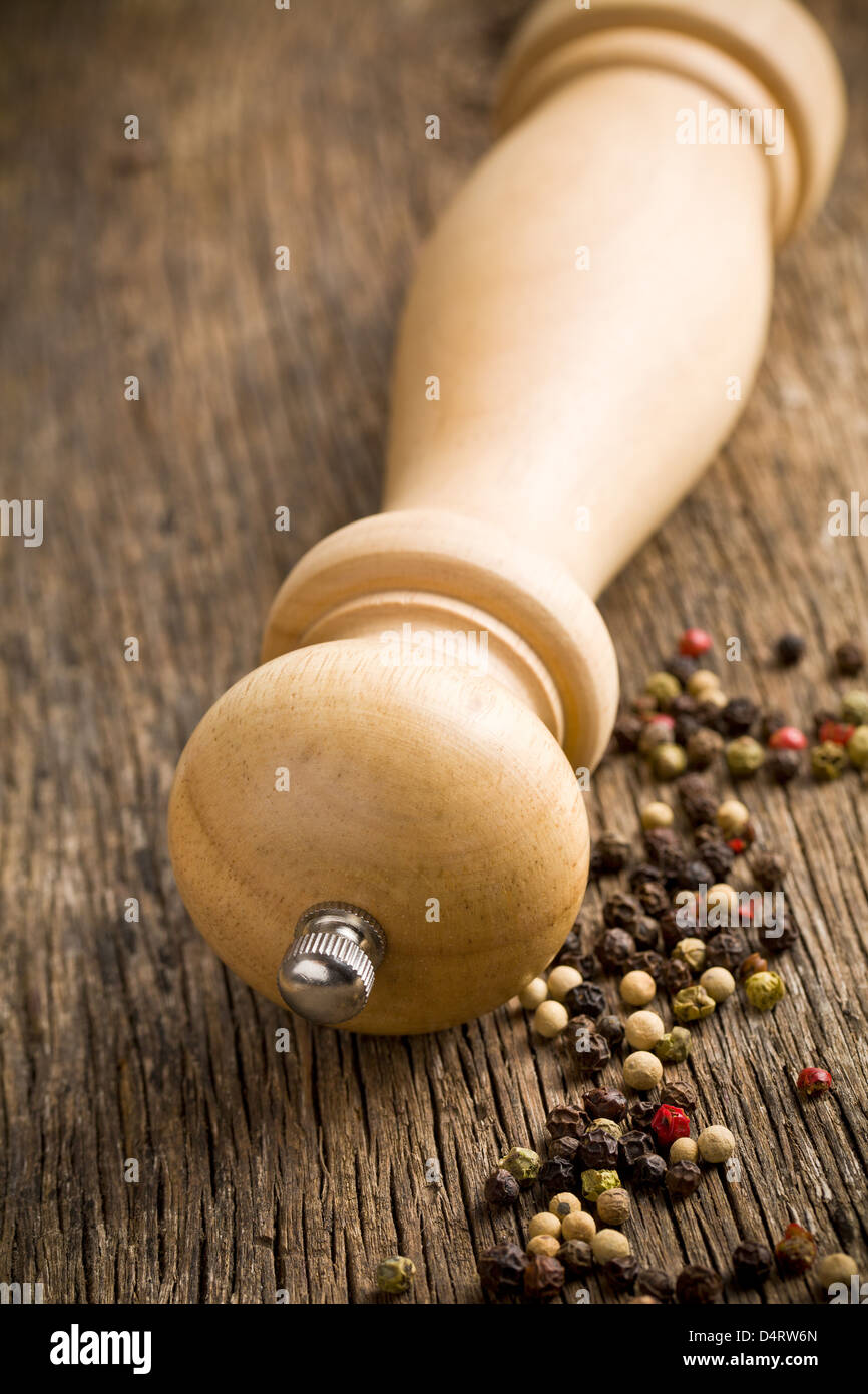 wooden pepper mill on old wooden table - Stock Image