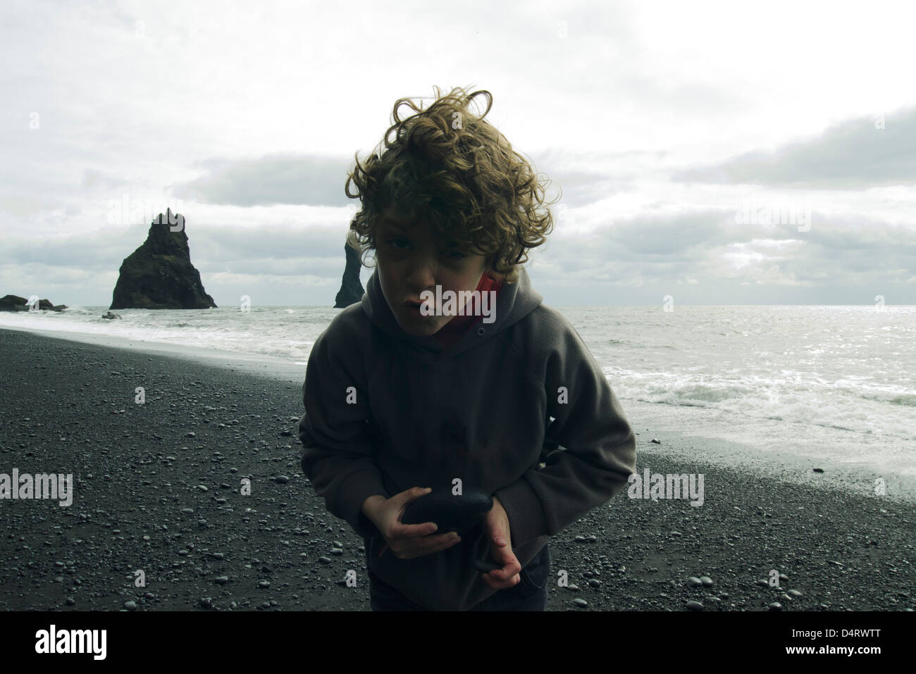 Grimacing boy on a beach iceland - Stock Image