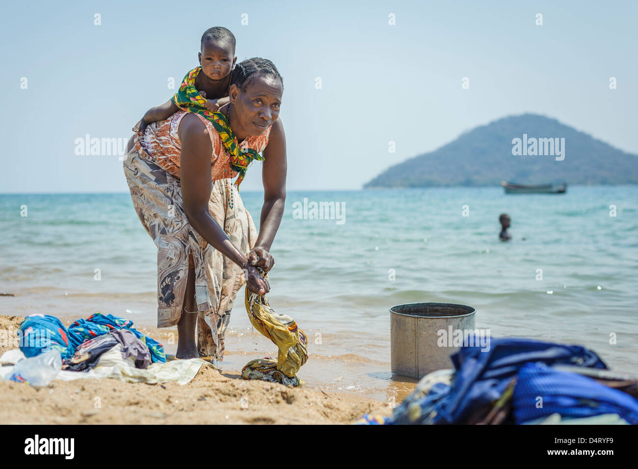 Woman with child washing clothes on the shore of lake Malawi, Malawi, Africa - Stock Image