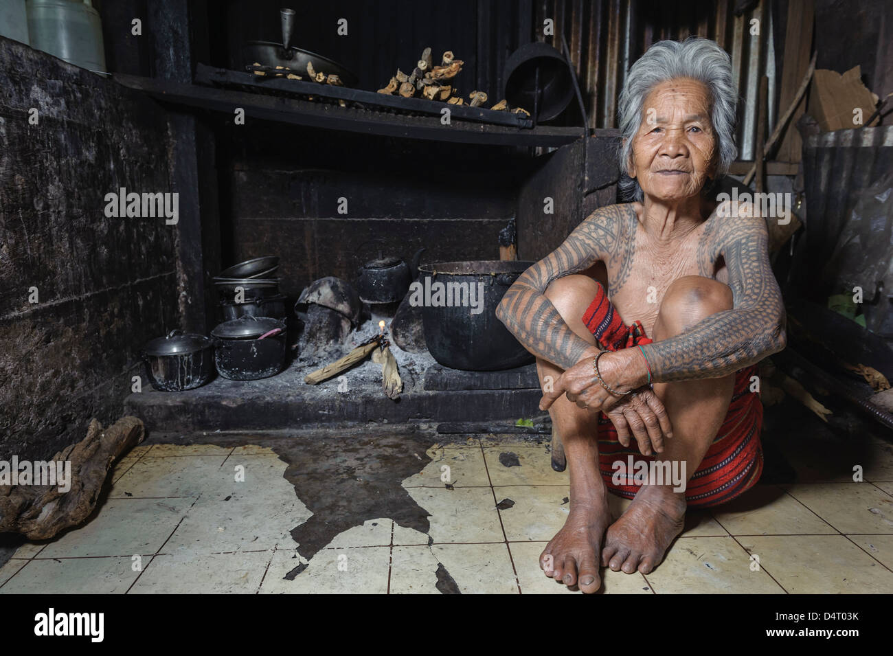 Ols tattooed woman from Tinglayan sitting by the fireplace, Luzon, Philippines. - Stock Image
