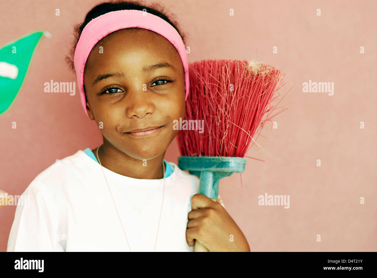 Africa, Angola, Luanda, portrait of an innocent African girl in a pink headband holding a red broom in front of - Stock Image