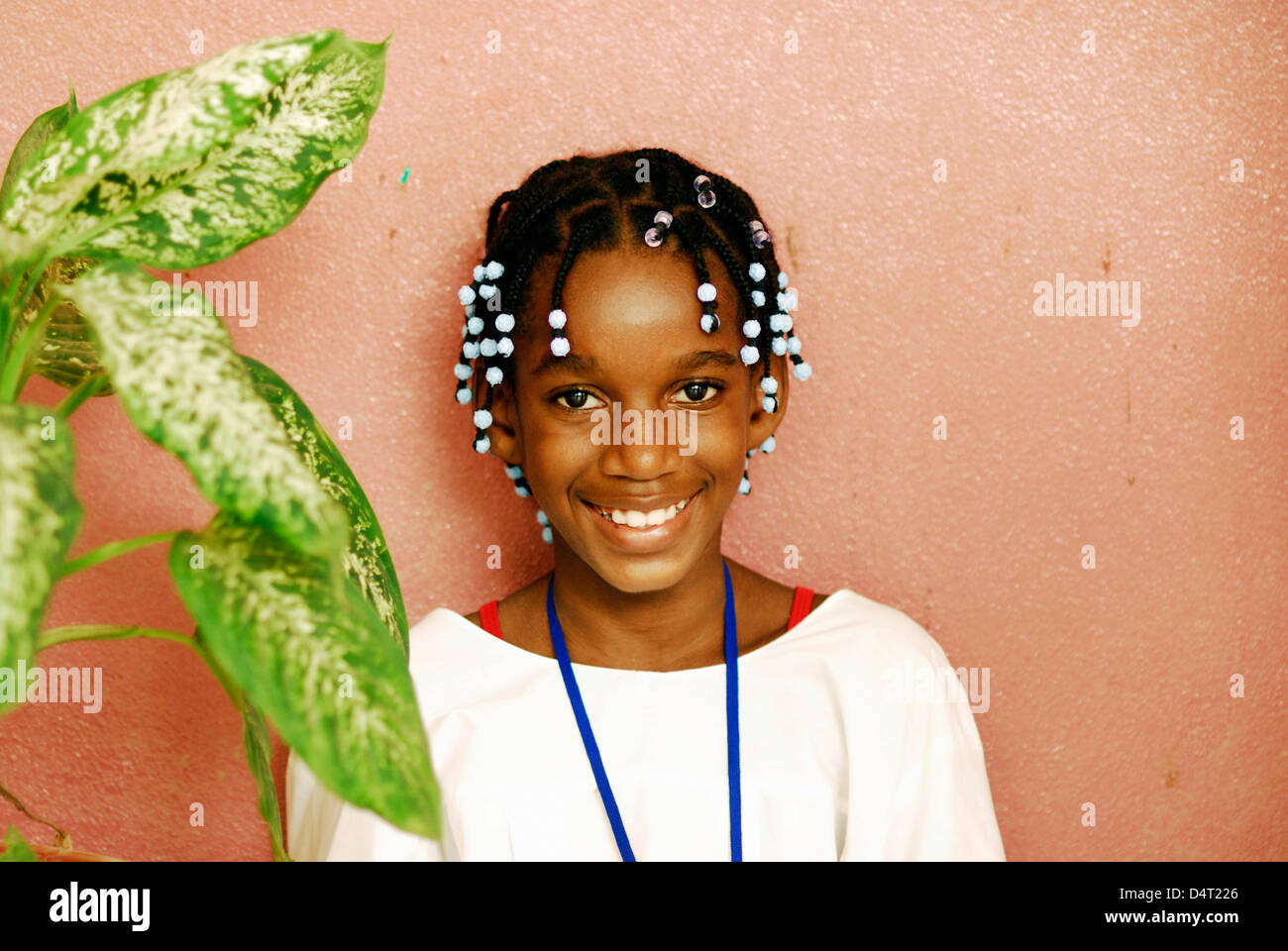 Africa, Angola, Luanda, portrait of an African girl with white beads in her braided hair smiling by a plant. (MR) - Stock Image
