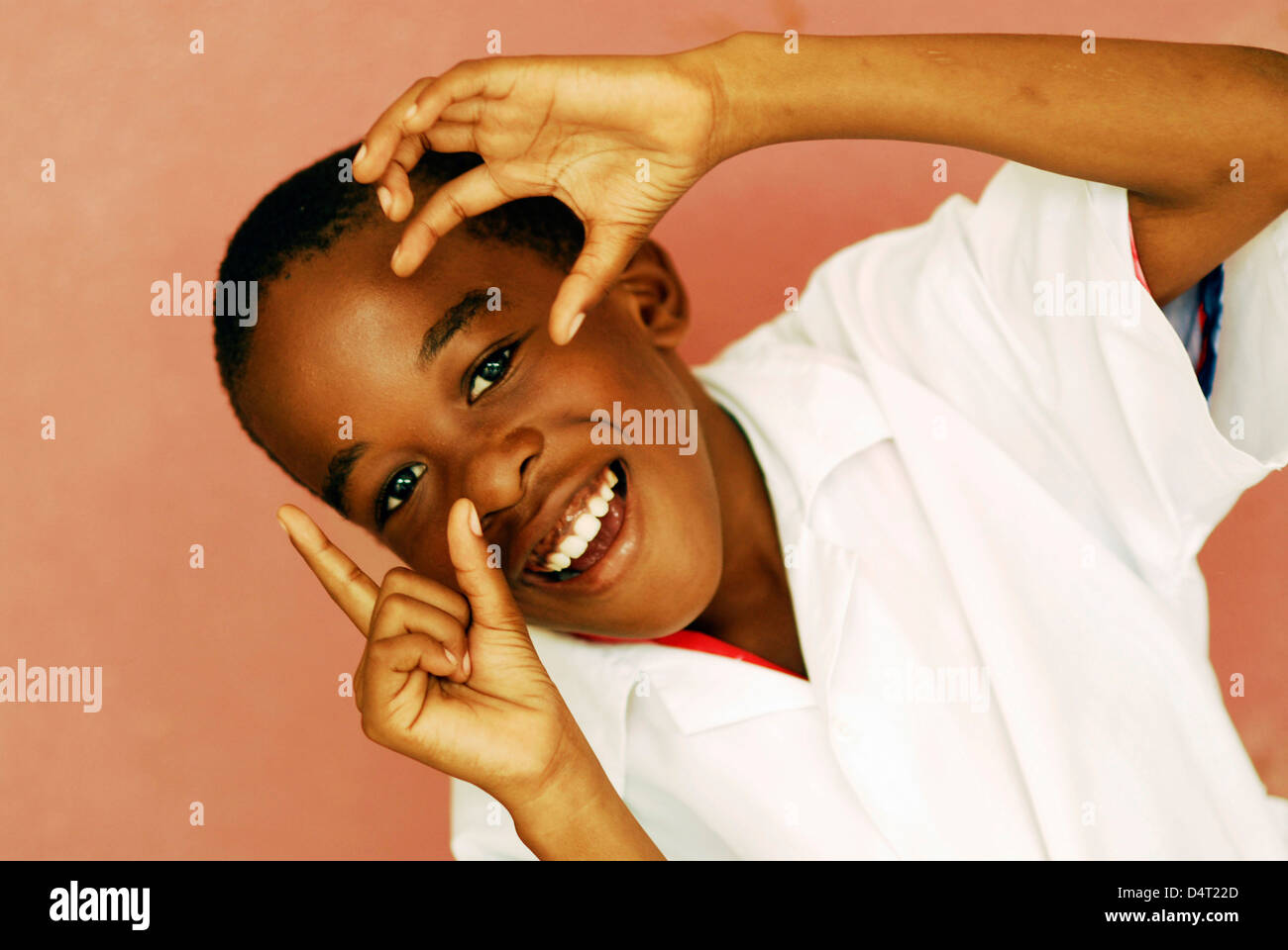 Africa, Angola, Luanda, close-up portrait of a cheerful little African boy in a white shirt gesturing. (MR) - Stock Image